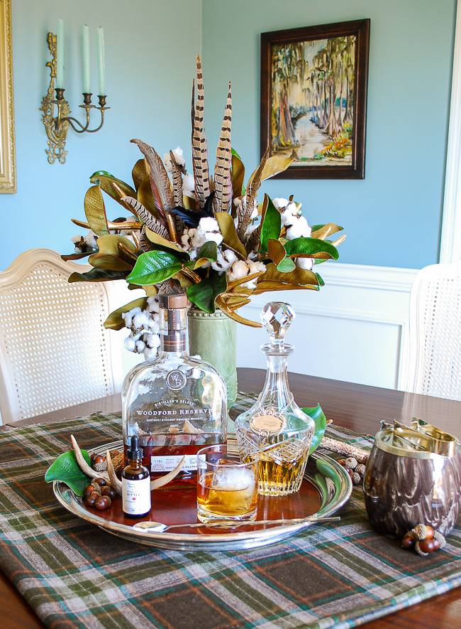 Bourbon and bitters on silver tray with feather, magnolia, and cotton floral arrangement