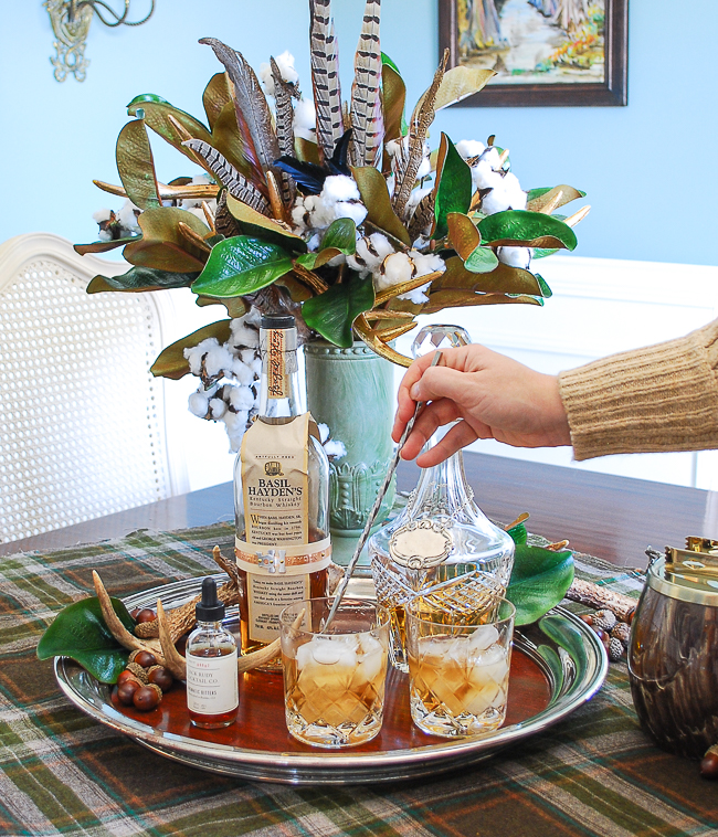 Two glasses of bourbon and bitters on silver tray with magnolia, feather, and cotton floral arrangement in background