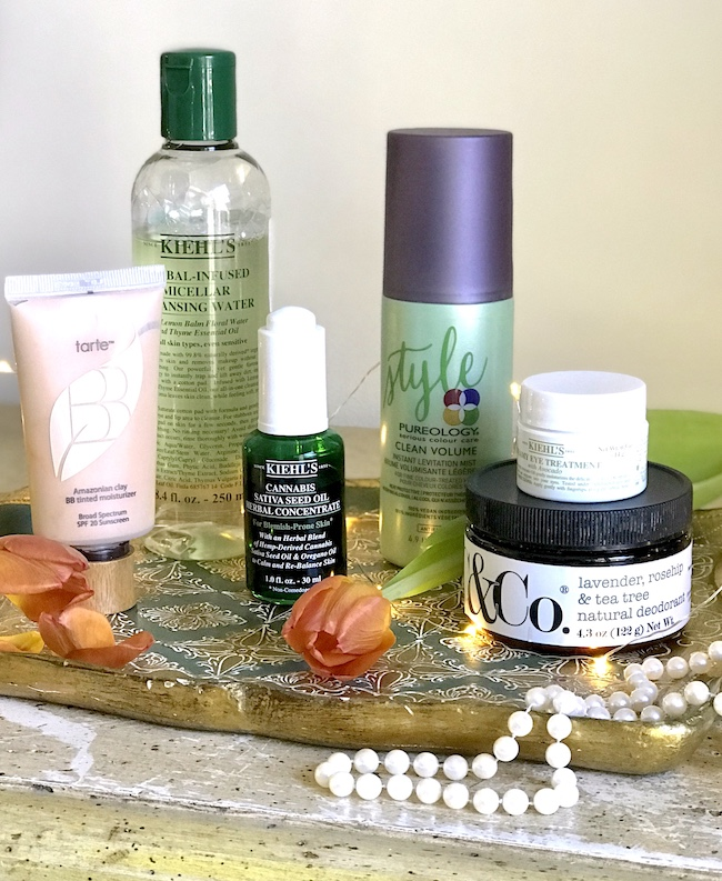 Group of fall beauty finds on Florentine tray with orange tulips and pearls
