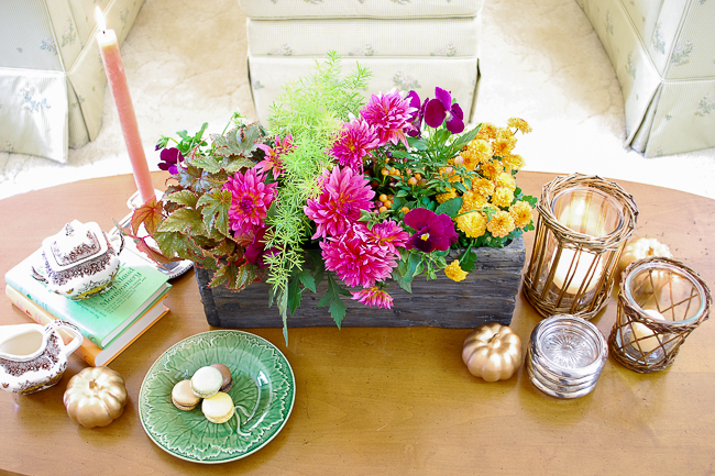 A coffee table vignette featuring a faux bois planter filled with flowers, wicker candle holders, and Majolica leaf plate.