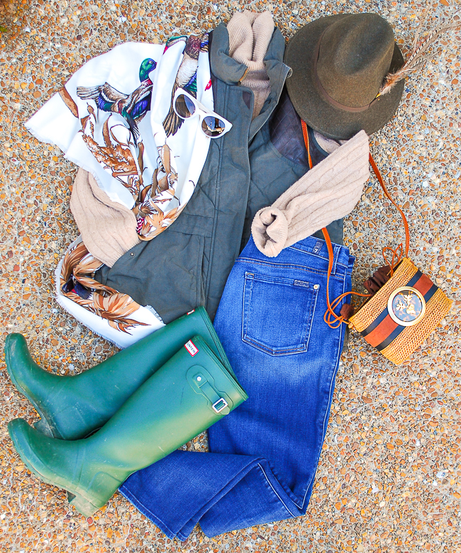 Flatlay of my casual fall uniform featuring jeans, cashmere sweater, quilted vest, scarf, and hunter rain boots