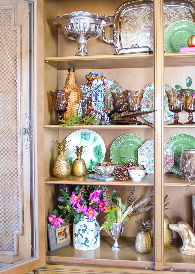 Try mixing metallics like brass and silver in your Majolica displays. Here vintage brass pineapples and silver tableware mingle with Majolica.