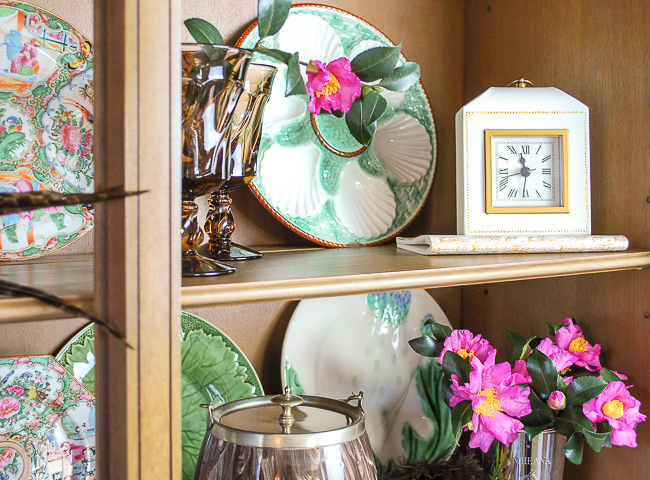 Majolica oyster plate displayed in bookcase with clock and pink camellias