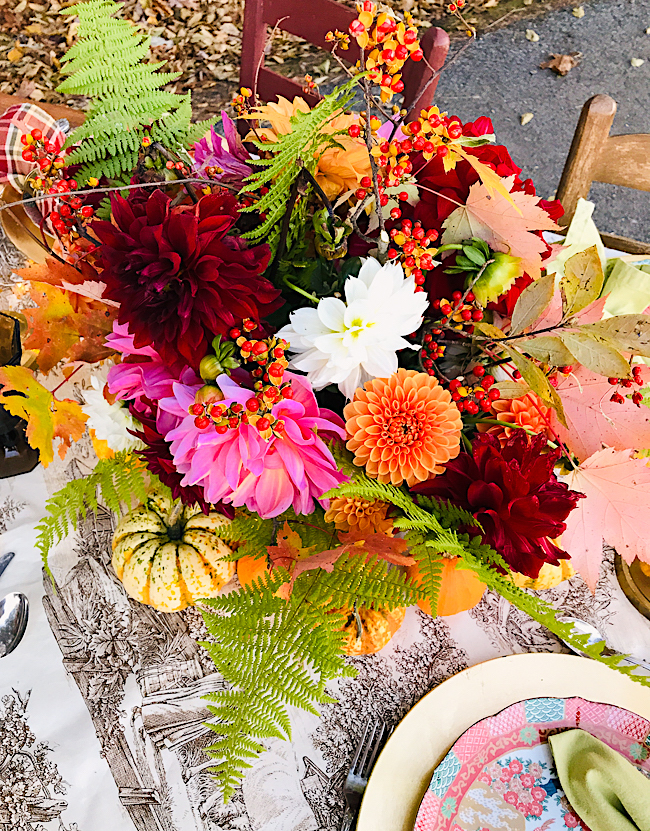 A riot of colorful dahlias, autumn foliage, bittersweet berries, and fern nestle in a brass bowl for this Thanksgiving table centerpiece.