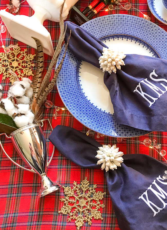 Navy blue monogrammed napkins and blue Mottahedeh china mix merrily on this red plaid tablecloth