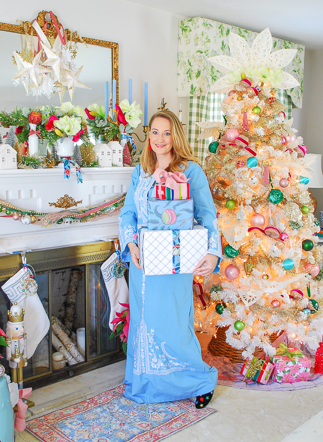 Katherine holds presents in front of colorful white Christmas tree with pops of pink and vintage charm