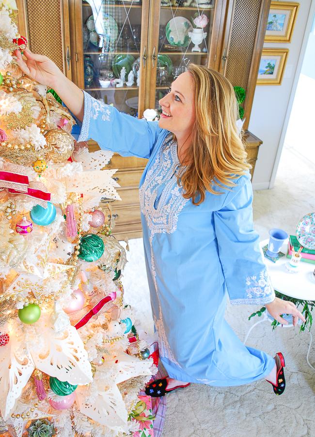 Katherine hanging an ornament on colorful Christmas tree