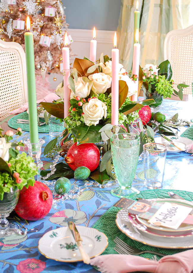 White roses, magnolia, pomegranates, and limes mingle in this centerpiece for a bold Christmas tablescape