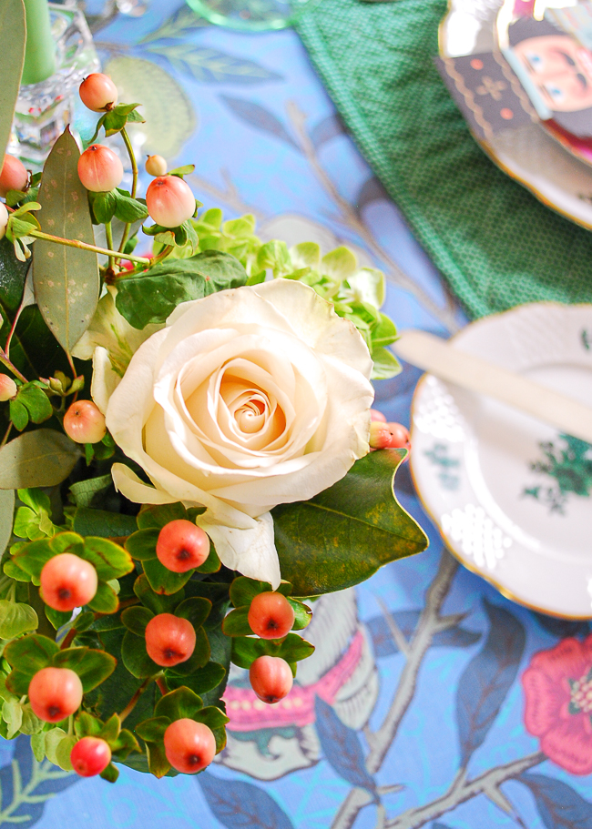 close-up of white rose floral arrangement on this bright colorful Christmas table