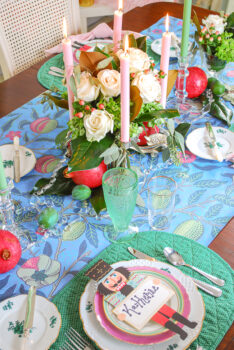 a bold Christmas tablescape set with a William Morris print, centerpiece of white roses and magnolia, polka dot placemats, and layered pink and green china