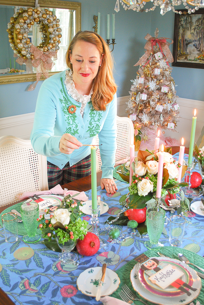 Katherine from Pender & Peony lights a candle on her pink and green Christmas table