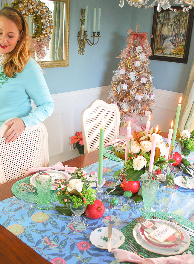 Blue, pink, and green Christmas table with white roses, magnolia, candlelight, pomegranate and lime runner