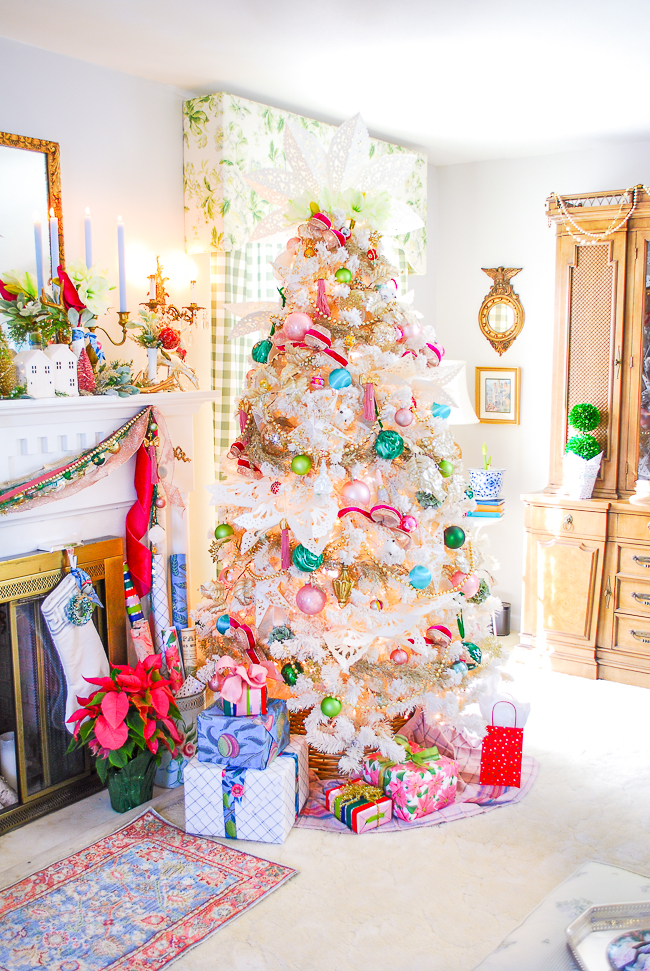 A white Christmas tree decorated with colorful, vintage ornaments, paper snowflakes, and pink ribbon