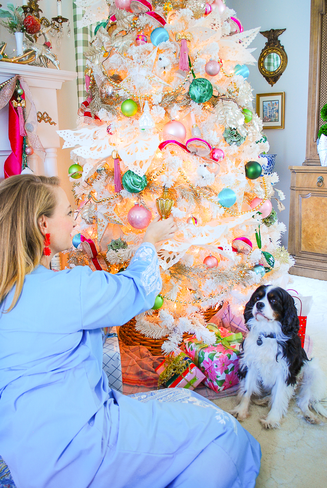 Katherine places ornaments on colorful white Christmas tree with pops of pink and vintage charm