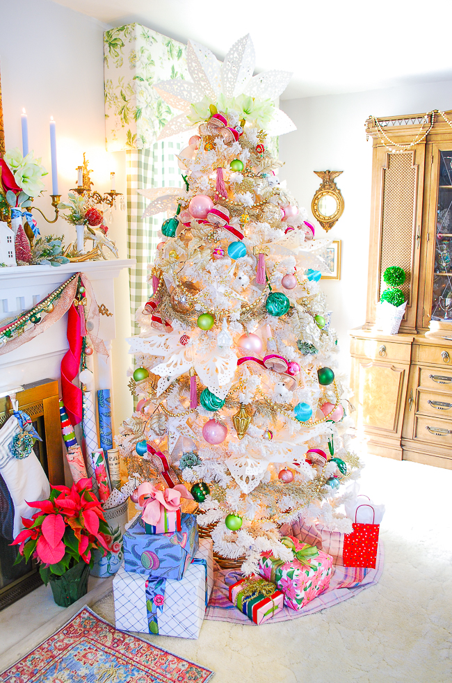 A chic and pink White Christmas tree decorated with vintage ornaments, paper snowflakes, glitter garland, and pink ribbon