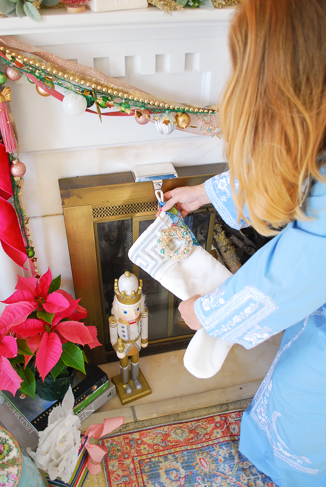 Katherine hangs white velvet stocking with Greek key border on fireplace