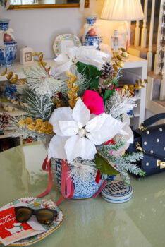 Front entry table with white poinsettia floral arrangement in blue and white ginger jar