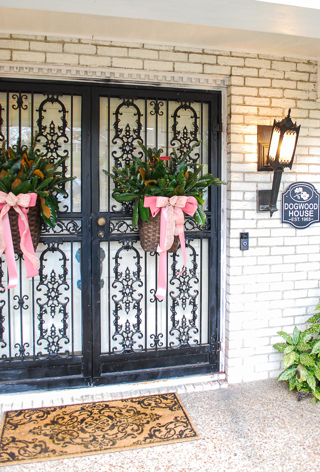 Katherine's front doors with baskets of pine and magnolia with pink bows