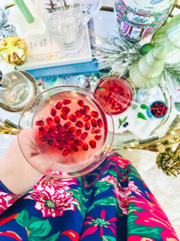 Top view of coupe filled with pomegranate gin cocktail for the holidays