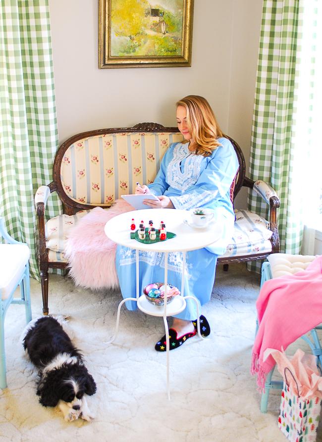 Katherine of Pender & Peony sitting on settee writing note in blue caftan