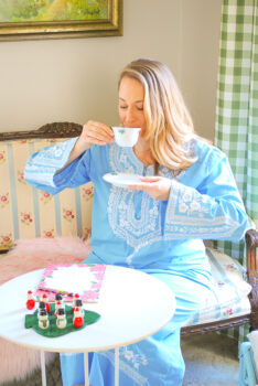 Katherine of Pender & Peony sitting on settee sipping tea in blue caftan