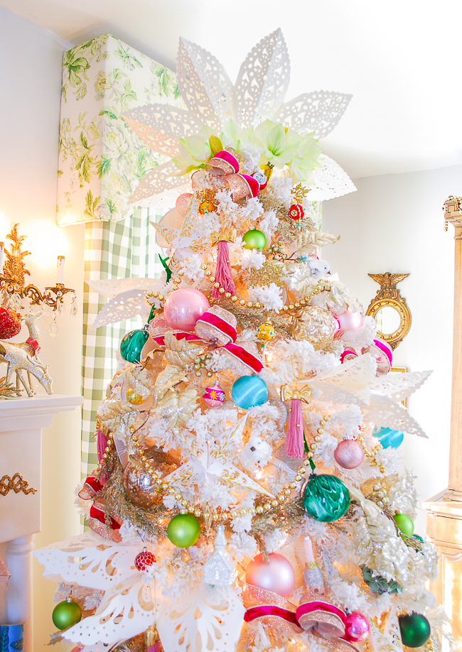 Colorful Christmas tree topped with white paper snowflake and amaryllis