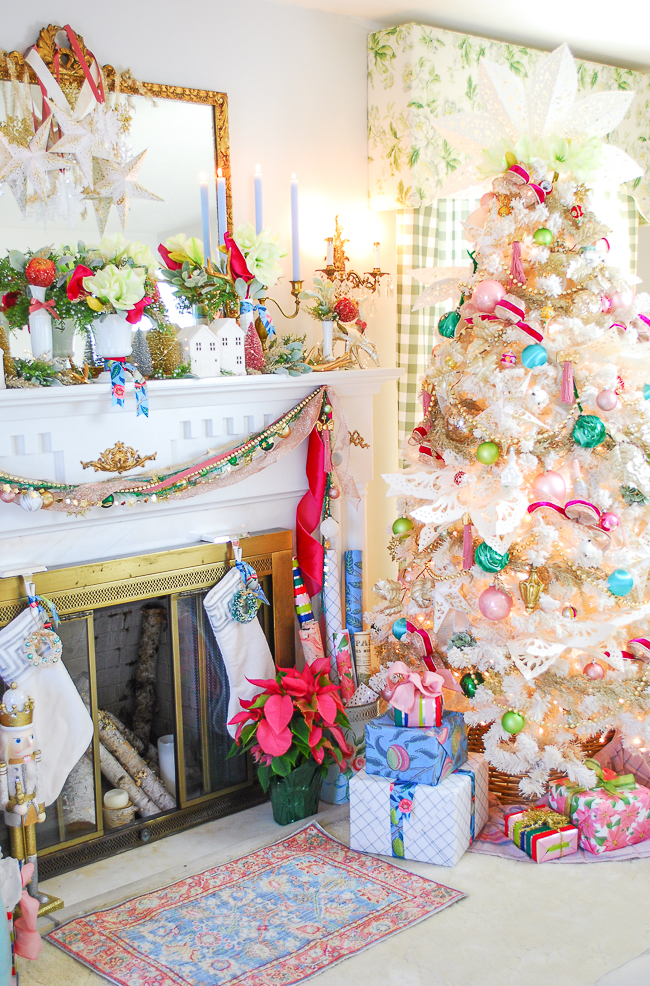 Chic and pink Christmas tree with whimsical holiday mantel complete this colorful living room