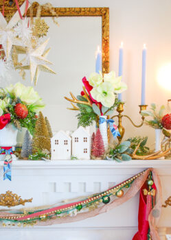 White ceramic houses on this Christmas mantel suggest a snowy winter village
