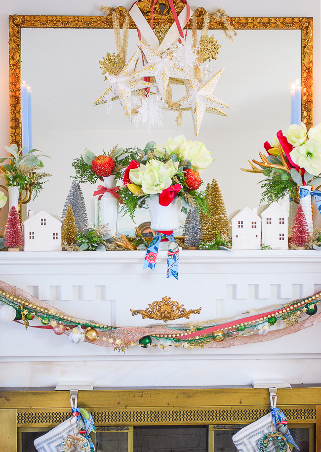 A whimsical Christmas mantel with amaryllis, white houses, milk glass, pink ribbon, and paper star lanterns
