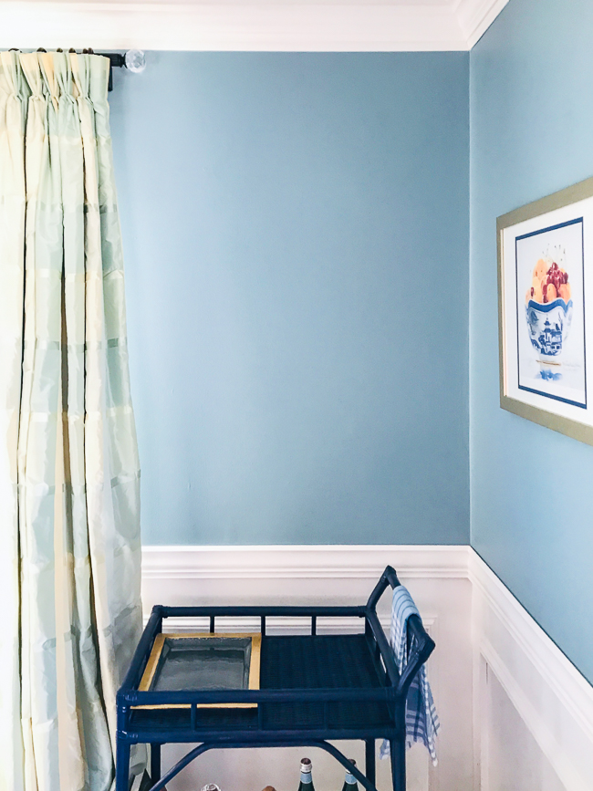 Grandmillennial dining room blank wall in interesting aqua paint with white wainscoting and plaid taffeta curtain - location for plate wall