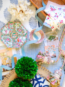 flatlay design board with grandmillennial decor, including boxwood, chinoiserie, magazine clippings, tassels, ribbon, chintz, and wicker