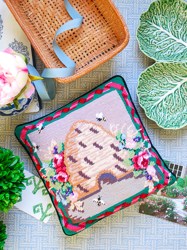 An essential grandmillennial decor item is needlepoint like this beehive pillow featured in this flatlay