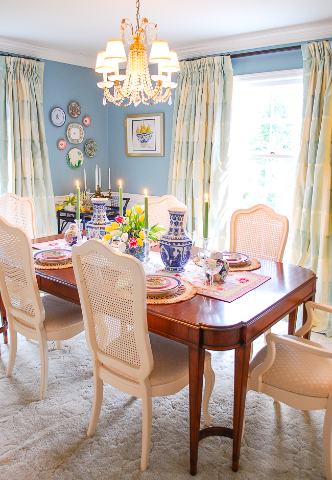 Grandmillennial dining room with bright pastel plate wall above rattan bar cart