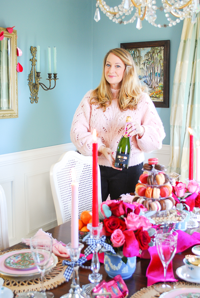 Katherine holds bottle of champagne in pink sweater