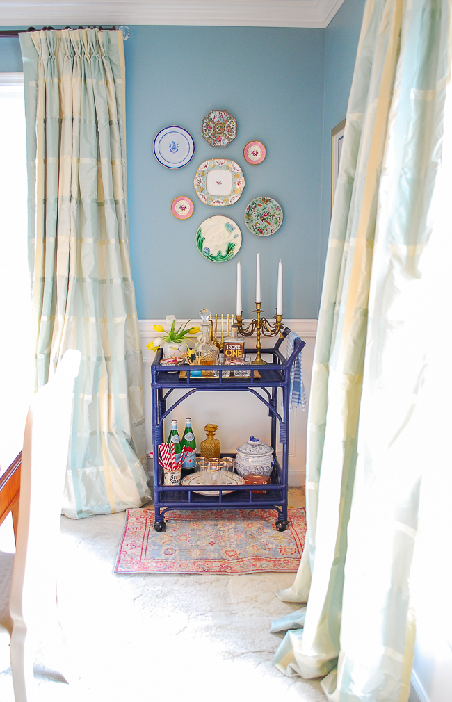 Grandmillennial dining room plate wall above navy blue rattan bar cart with antique plates in bright pastels, including famille rose, majolica, and Sèvres style
