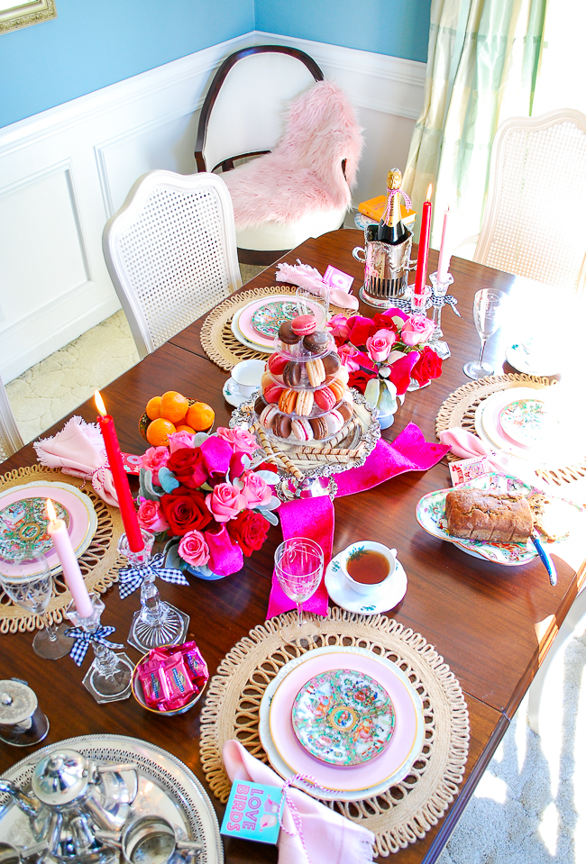 Red and pink tablescape set for a Valentine's tea party with macaron tower centerpiece and rose medallion china