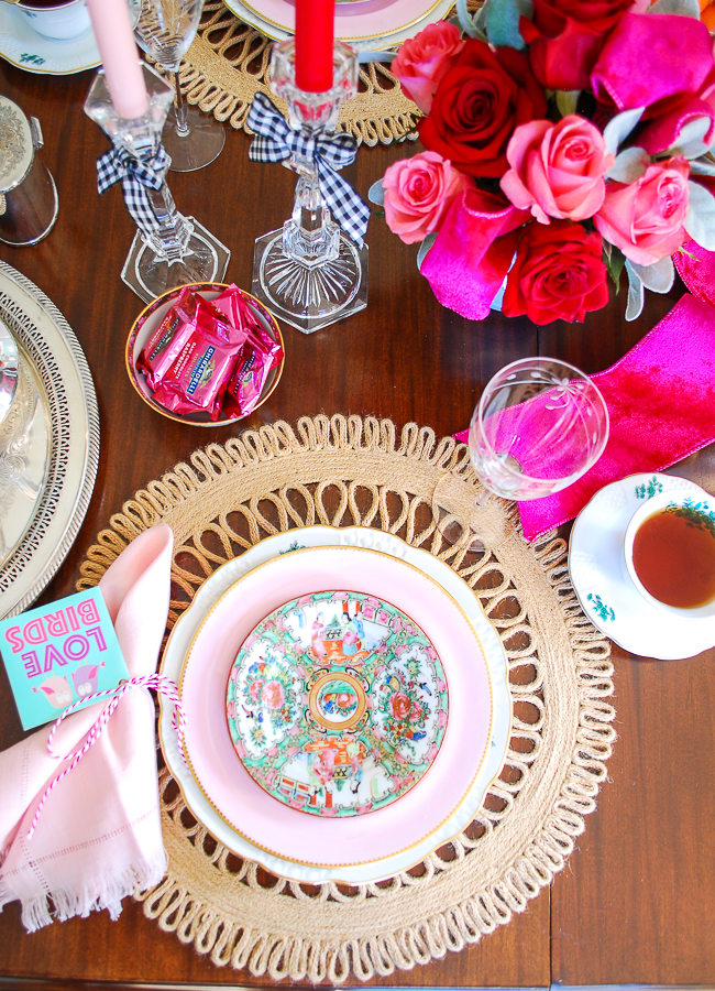 Pink place setting with rose medallion plates, etched champagne glass, green floral cup, pink napkin, and round scalloped jute charger
