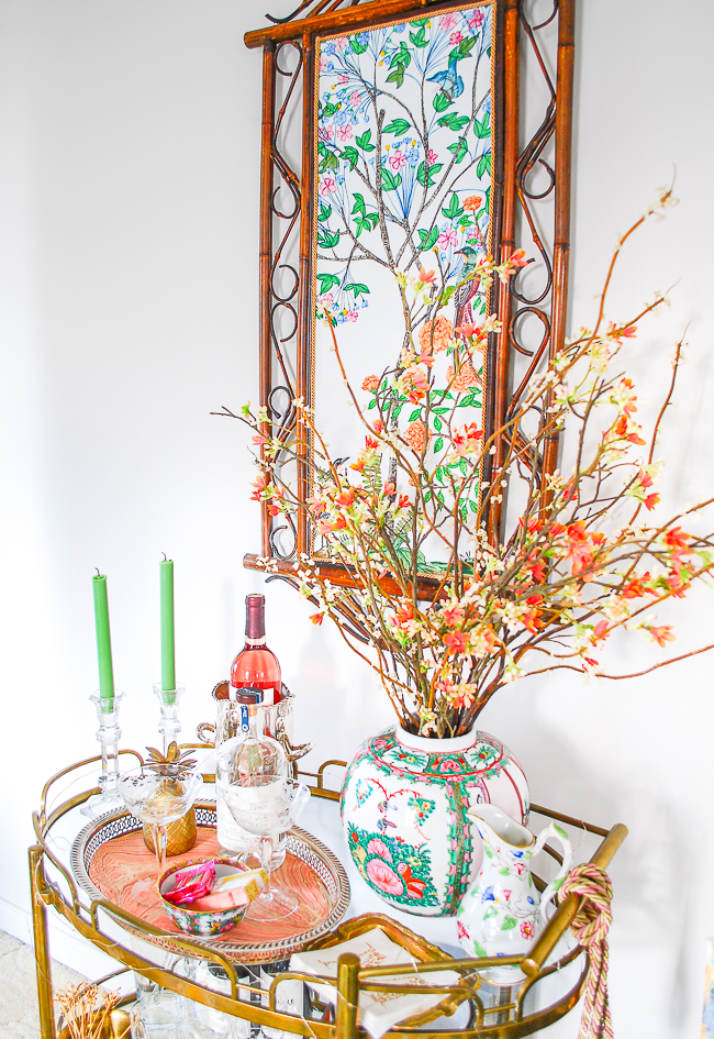 Chinoiserie panel above vintage bar cart with blossoming branches in rose medallion jar