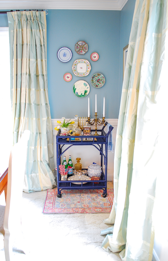 navy rattan bar cart with plate wall above in this traditional aqua dining room