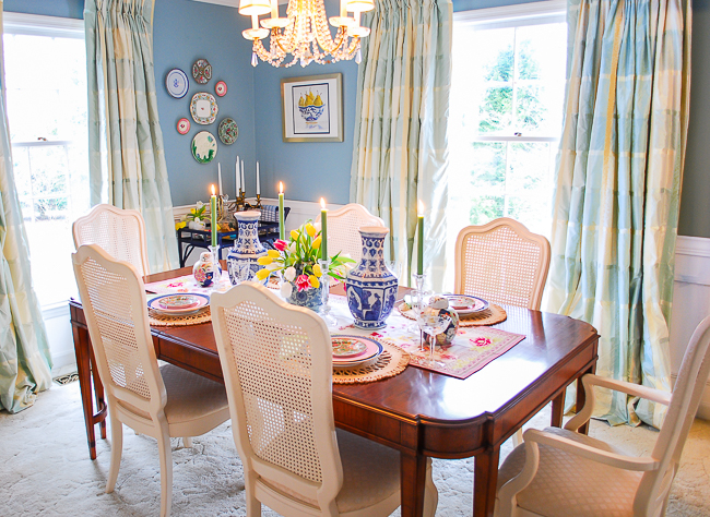 Side view of grandmillennial style dining room with aqua walls, wainscoting, crystal chandelier, plate wall, and antique furniture