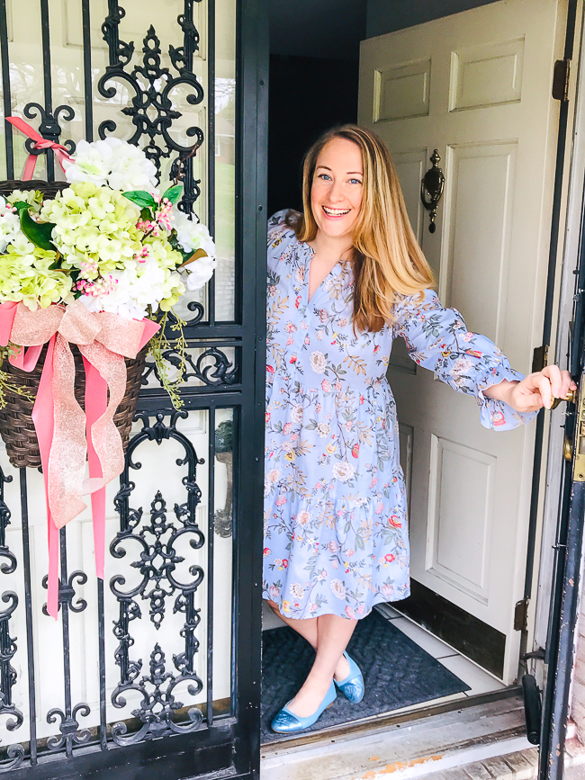 Katherine in Gal Meets Glam dress leans out front door welcoming you to the Blooming for Spring - Southern Home Tour