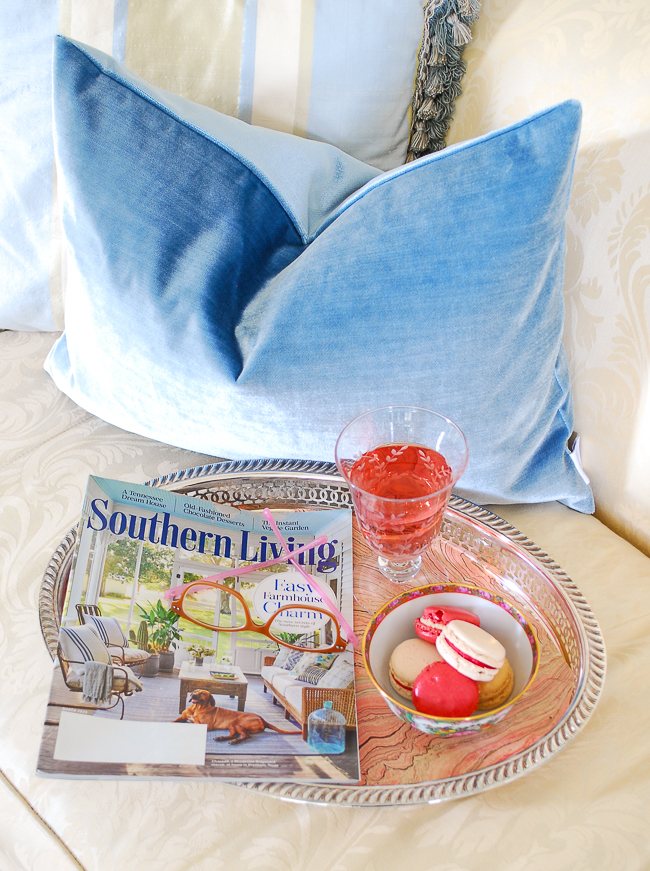 Blue velvet pillows and a silver tray of macarons and wine with Southern Living magazine
