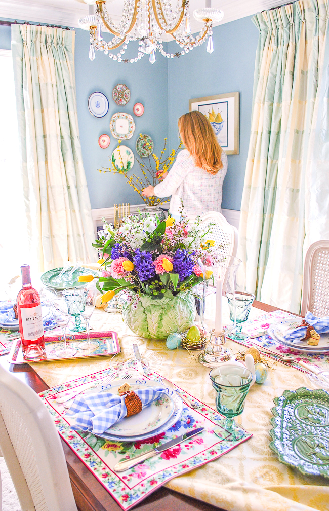 Dining table set with fresh traditional Easter tablescape in bright pastels, spring florals, and April Cornell placemats. Katherine arranges flowers in background.