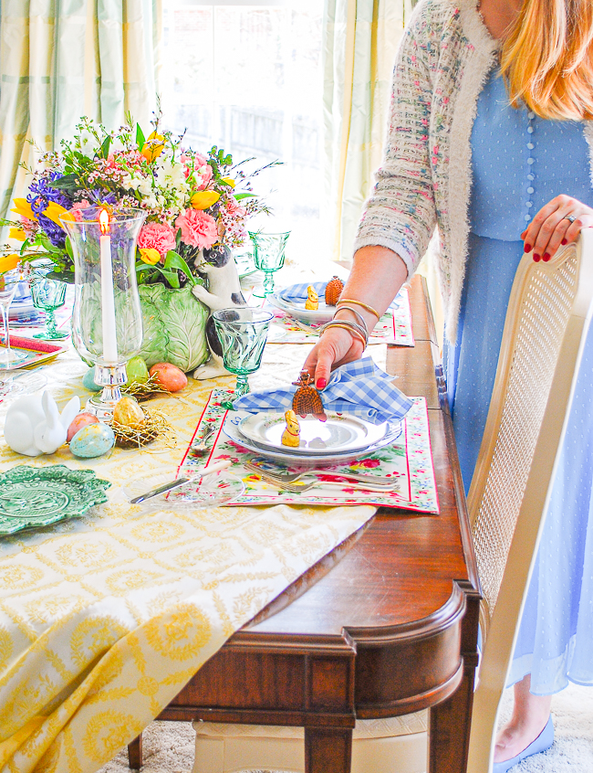 Katherine in blue spring dress and tweed cardigan places gingham napkin on table setting