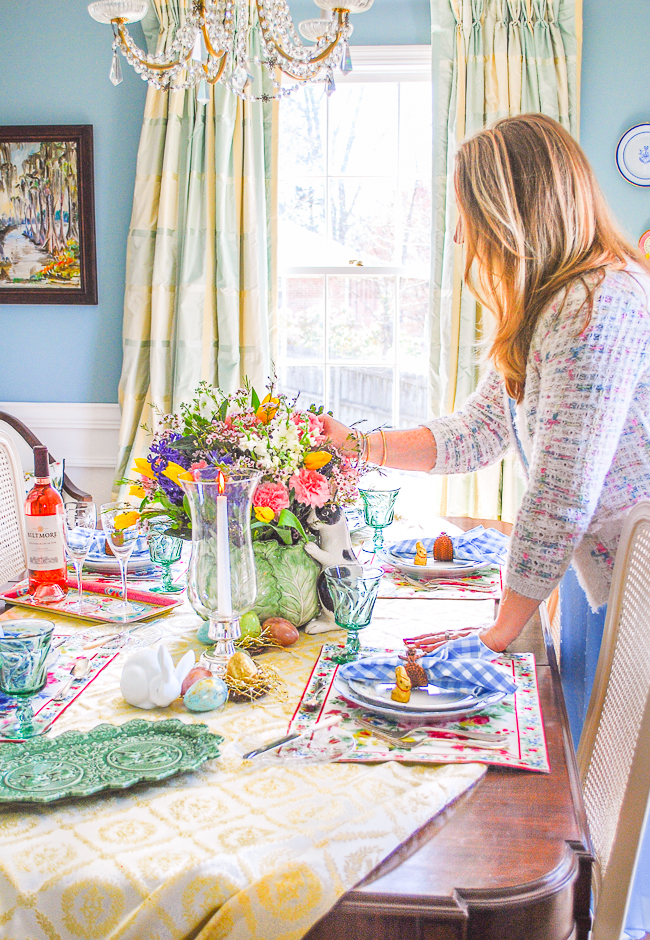 Katherine adjusts flowers in centerpiece on spring table