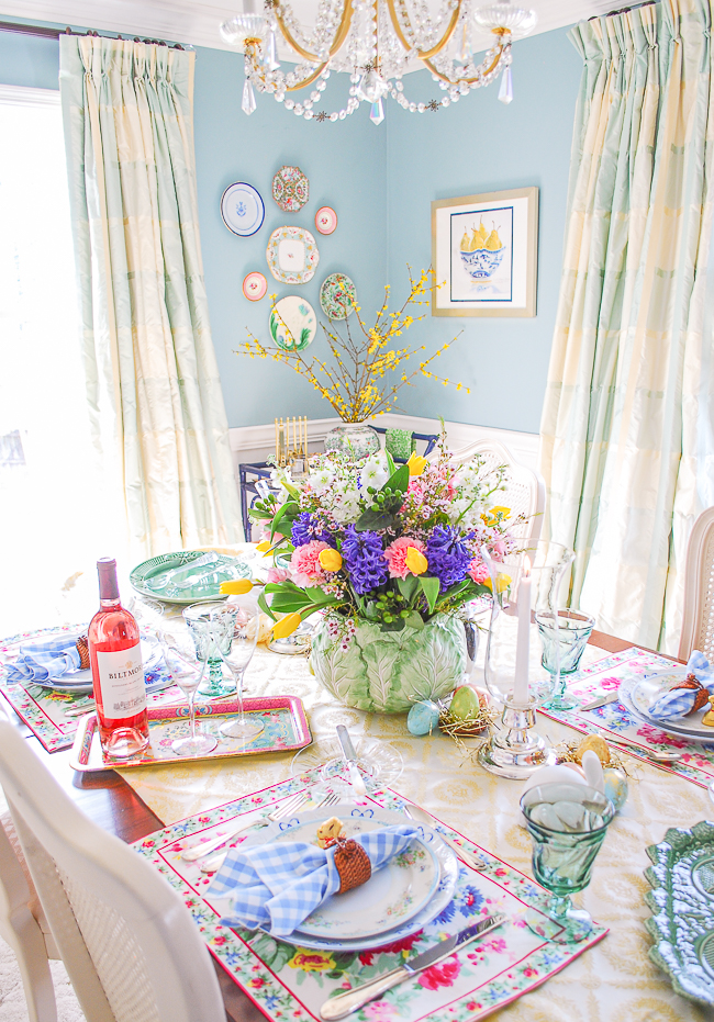 Dining table set with fresh traditional Easter tablescape in bright pastels, spring florals, and April Cornell placemats.