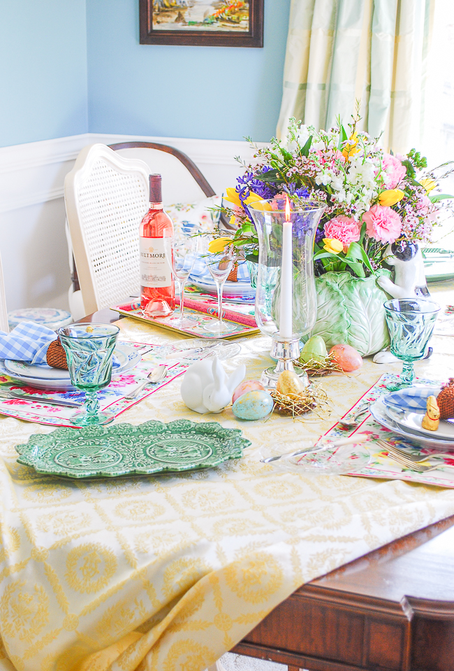 Easter tablescape set with yellow tablecloth, Pinheiro Bordallo bunny platters, Vista Alegre china, April Cornell placemats, and gingham napkins. Centerpiece is Fitz & Floyd cabbage bunny with spring florals