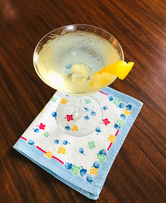 An effortless French 75 champagne cocktail in coupe with floral linen napkin