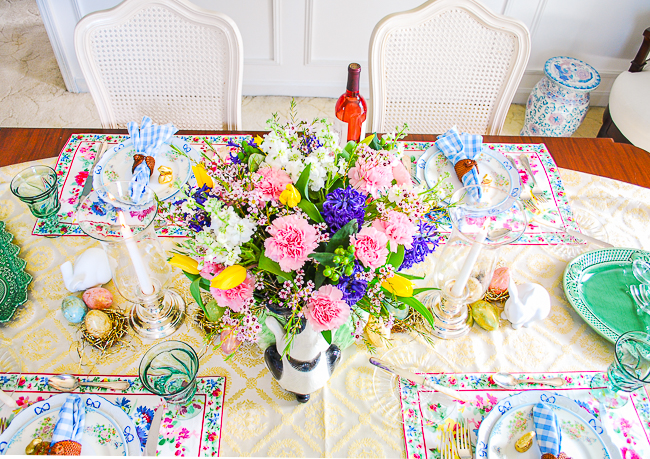 Easter table with spring florals in bunny cabbage ware bowl, yellow runner, and floral placemats