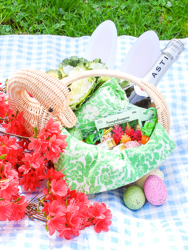 Wicker swan basket for adult Easter basket inspiration filled with bottle of champagne, flower seed packets, pretty dish towels, and candy.